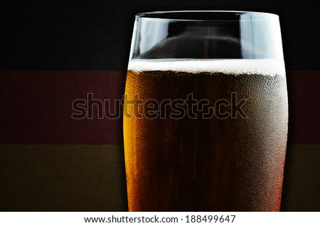 A glass of beer. Germany flag in the background. One of the countries where beer consumption is highest in the world. - stock photo