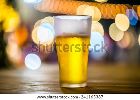 A glass of beer with bokeh light background. - stock photo