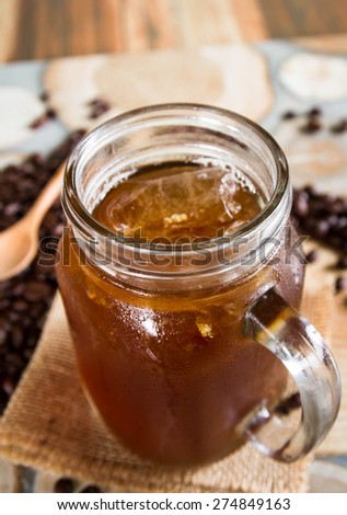 A glass of black iced coffee surrounded by coffee beans. - stock photo