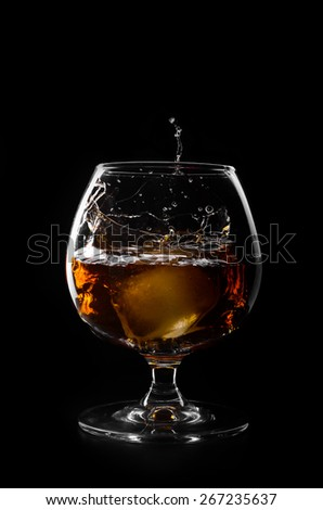 A glass of brandy and ice cube on a black background - stock photo