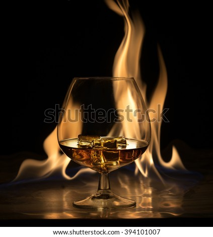 A glass of brandy and ice, on a background of fire - stock photo