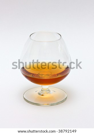 A glass of cognac on white background. - stock photo