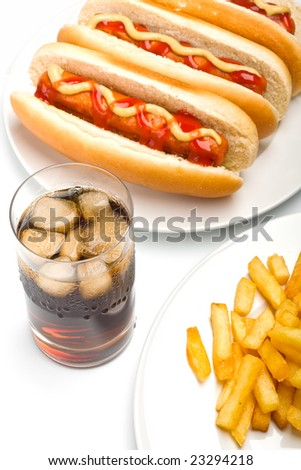 a glass of cola, french fries and three classic hotdogs with mustard and ketchup on a plate - stock photo