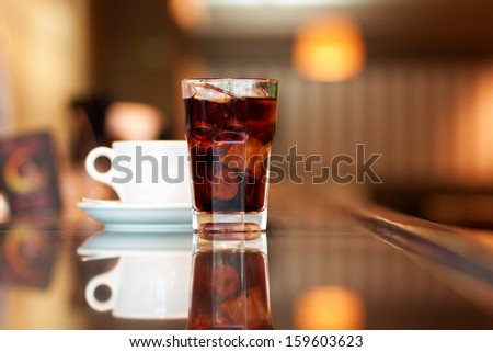 A glass of cola or soda with ice cubes and cup of black coffee on the bar - stock photo