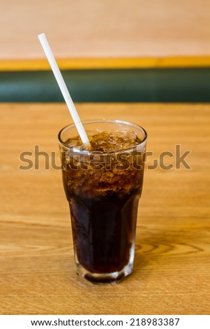 A glass of cola with ice cubes on the wood table. - stock photo