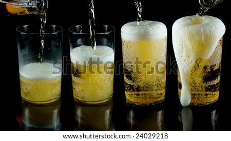 A glass of cold beer with foam on a black backgraund - stock photo