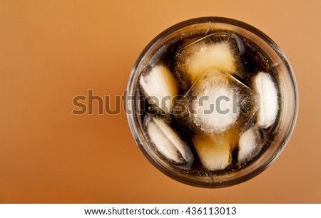 a glass of cold drink with ice on brown background closeup - stock photo