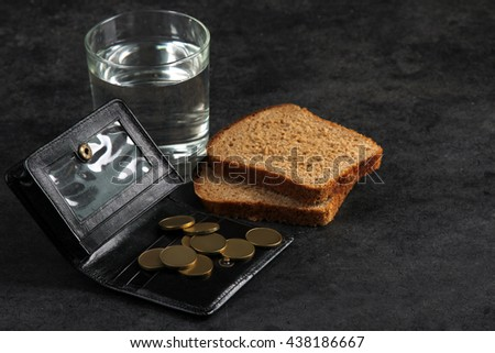 a glass of drinking water and pieces of bread near cents on the purse on a black background.The concept of poverty - stock photo