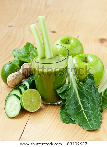 A glass of fresh apple, lime, ginger, celery, chard and cucumber juice, shallow depth of field - stock photo