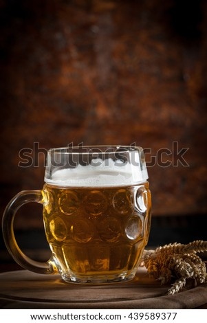 A glass of fresh cold light beer with gourmet hamburgers and wheat in a bar and a dark pub - stock photo