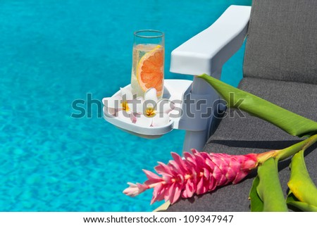 A glass of fresh lemonade, frangipani flowers and torch Ginger flower on resting chair, by swimming pool - stock photo
