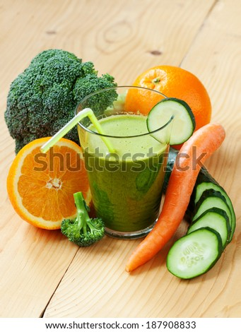 A glass of fresh orange, carrot, broccoli and cucumber juice, shallow depth of field - stock photo