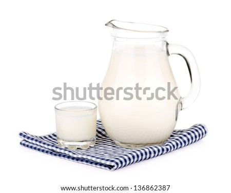 A glass of milk and a milk jug on plaid tablecloth. - stock photo