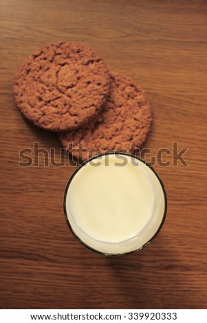 A glass of milk and chocolate cookies on wooden background, top view. - stock photo