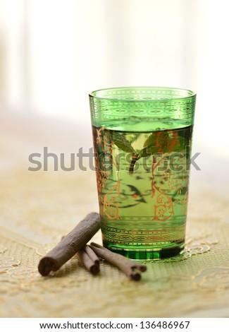 A glass of Moroccan tea and cinnamon. - stock photo
