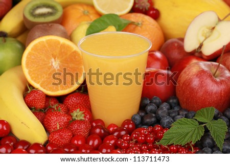 A glass of orange smoothie surrounded by fresh fruits - stock photo