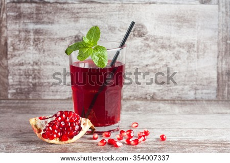 A glass of pomegranate juice with fresh pomegranate fruits on wooden table. Vitamins and minerals. Healthy drink concept. - stock photo