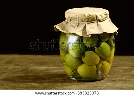 A glass of preserved olives - stock photo