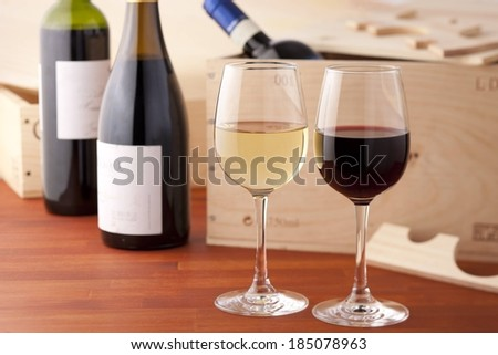 A glass of red and white wine on a table with bottles of open wine. - stock photo
