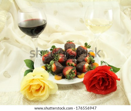 A glass of red and white wine with chocolate covered strawberries, chocolate covered apricots and roses. - stock photo