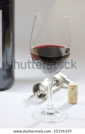 a glass of red wine, a corkscrew, a cork and a wine bottle - stock photo