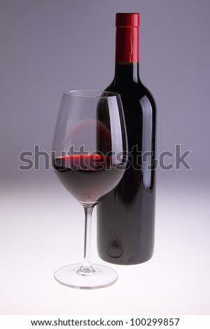 A glass of red wine and bottle - stock photo