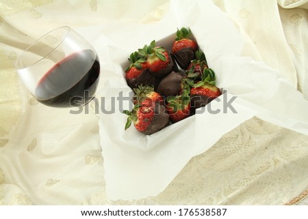 A glass of red wine and box of chocolate strawberries. - stock photo