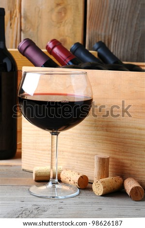 A glass of red wine in front of a wooden case of wine bottles on a rustic wood background. Vertical Format. - stock photo