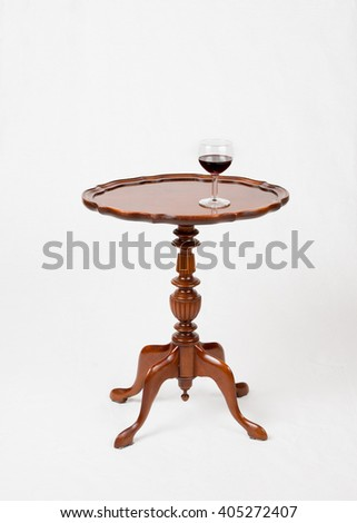 A glass of red wine on vintage wine table, cherry finish, isolated in white background. - stock photo