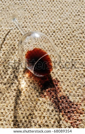 A glass of red wine spilt on a wool carpet. - stock photo