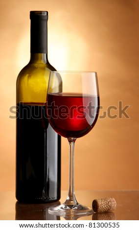 A glass of red wine with a bottle on a table - stock photo