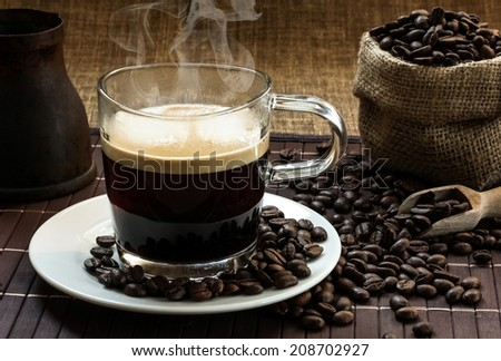 A glass of steaming hot fresh espresso coffee on a white plate with a bag of coffee beans in the background - stock photo