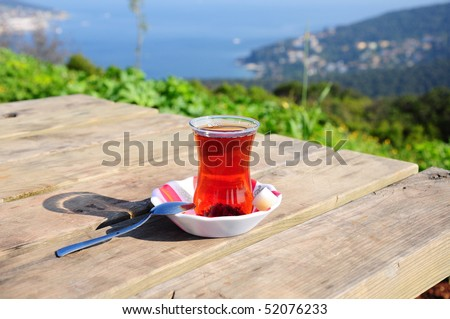 a glass of tea on a wooden table on nature - stock photo
