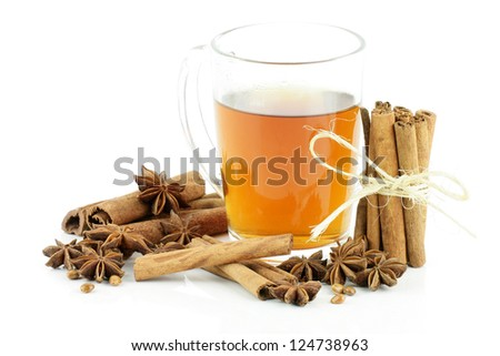 A glass of tea with cinnamon and star anise, on a white background. - stock photo
