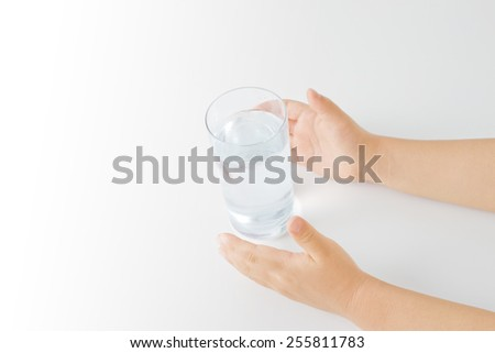 a glass of water and child's hands - stock photo