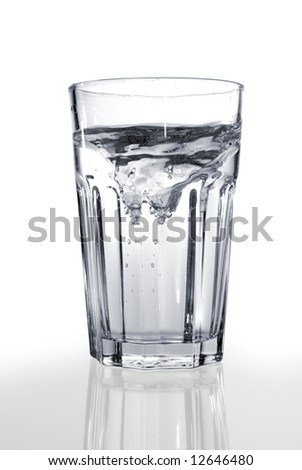 A glass of water on a reflective surface - stock photo