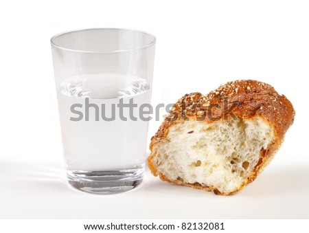 A glass of water with a piece of bread - stock photo