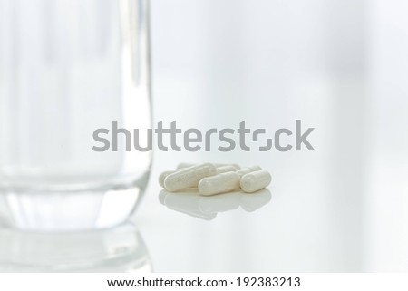 A glass of water with white pills nearby. - stock photo