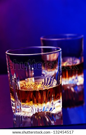 a glass of whiskey against two colored background - stock photo