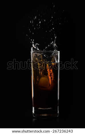 A glass of whiskey and ice cube on a black background - stock photo