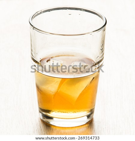 A glass of whisky with ice on wood table. - stock photo