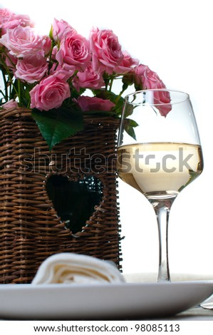 A glass of white wine and a basket of roses on the table - stock photo