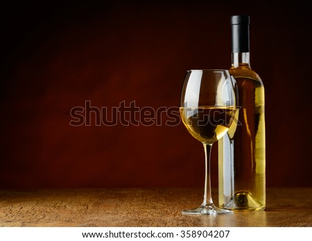 A glass of white wine and a bootle of white wine oni a wooden table in a a winecellar - stock photo