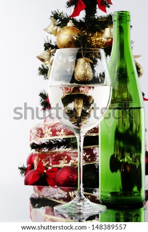 a glass of white wine and green bottle against Christmas tree at background  - stock photo