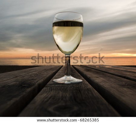 A glass of white wine at sunset next to the sea - stock photo
