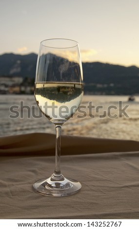 A glass of white wine with view of a lake - stock photo