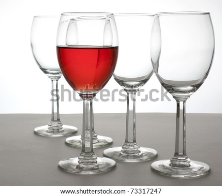 A glass of White Zinfandel and four empty wine glasses - stock photo