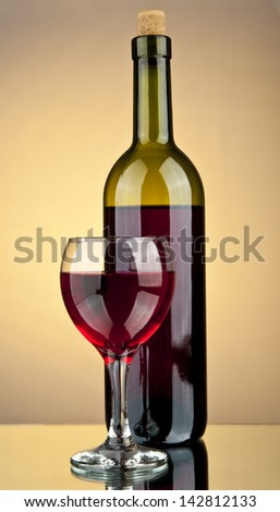 a glass of wine and a bottle on a yellow background - stock photo