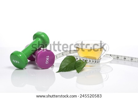 A glass tea pot and cup with dumbbells, tape measure, leaf isolated white at the studio. - stock photo