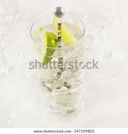 A glass tumbler of gin and tonic with ice and fresh sliced lime.  - stock photo